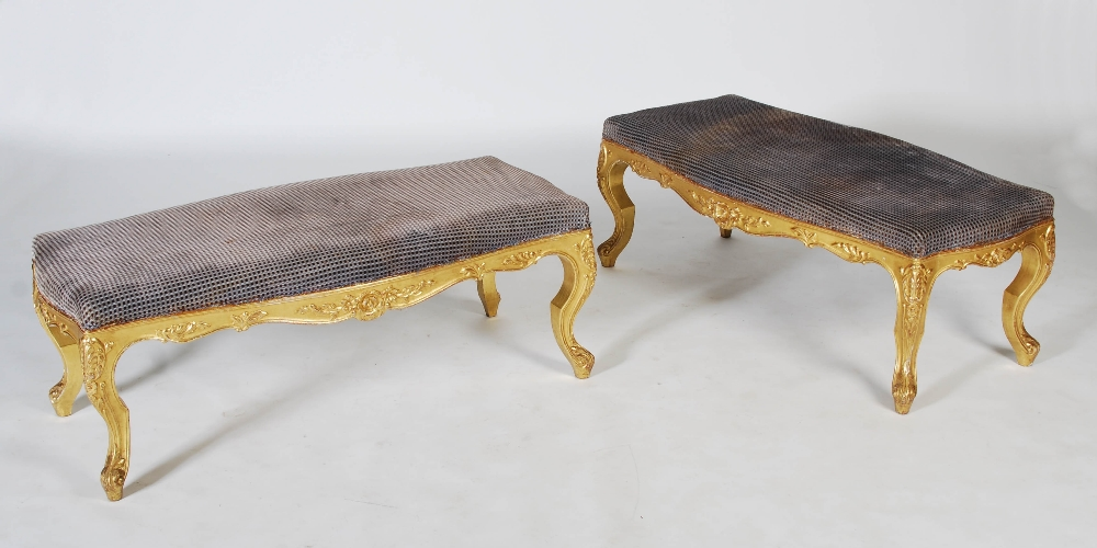Lot 104 - A pair of Victorian style gilt wood stools, the rectangular upholstered tops with a serpentine edge,