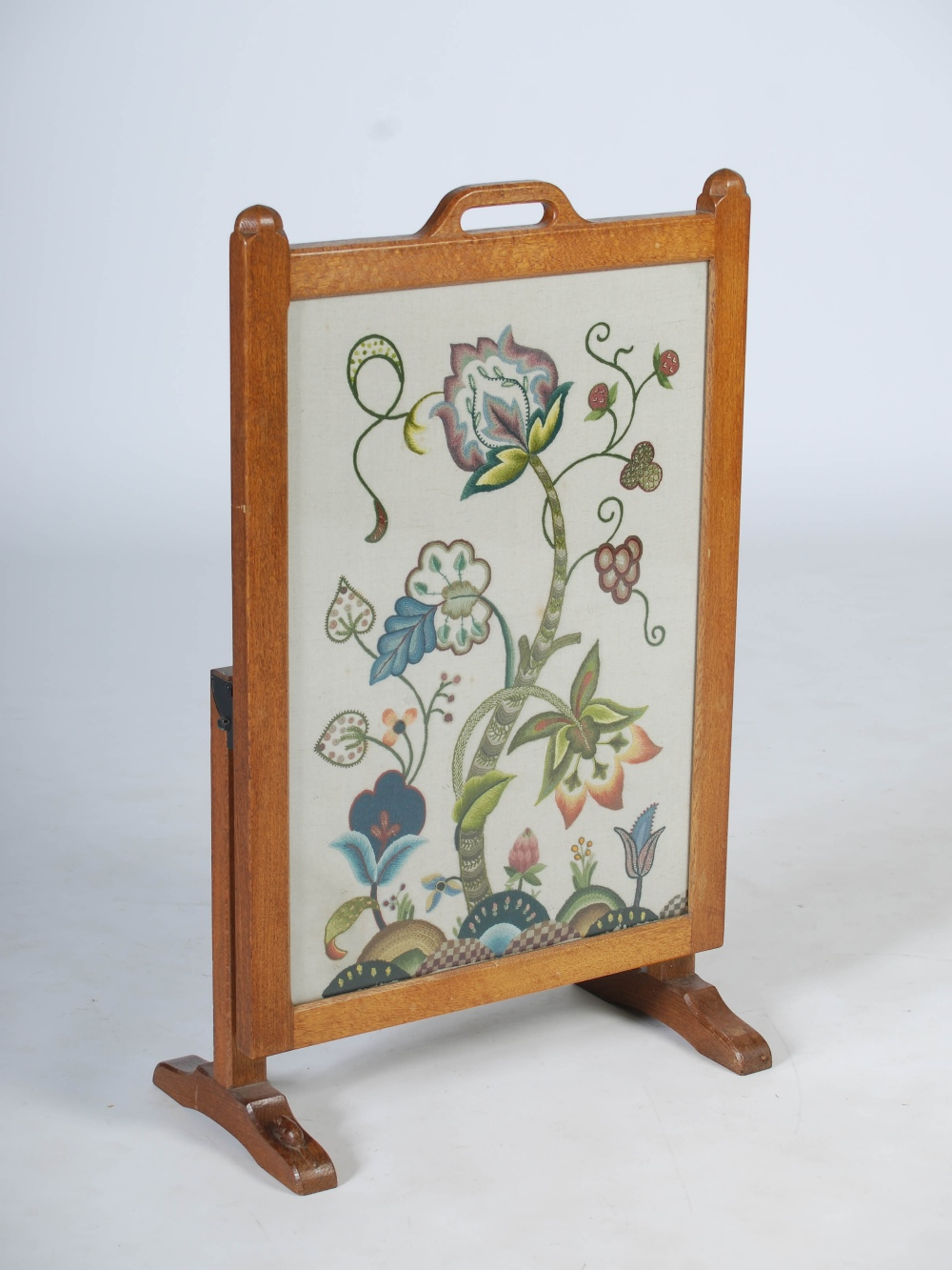 Lot 113 - A carved oak fire screen by Beaverman, the hinged rectangular screen with needlework upholstered