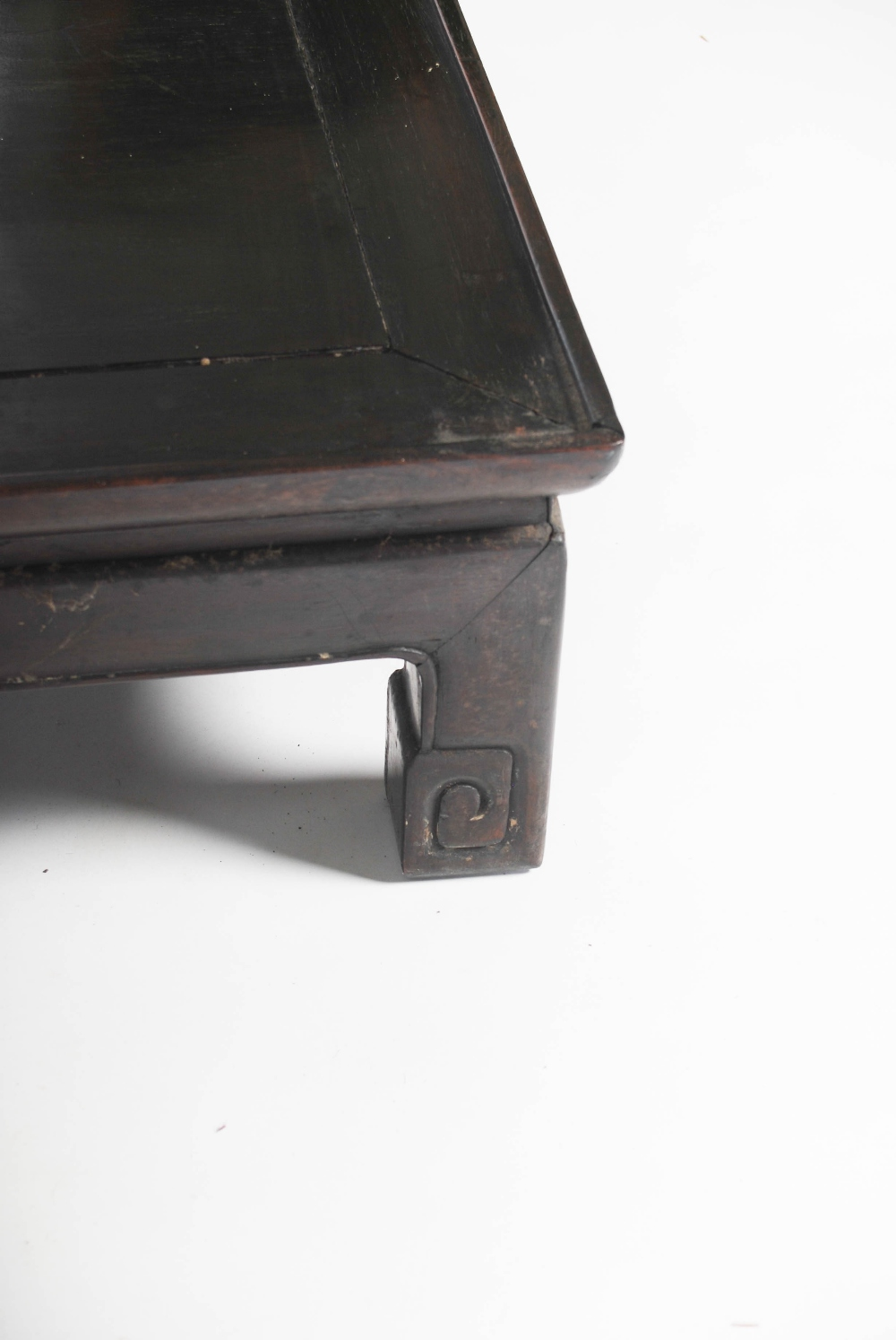 Lot 40 - A Chinese dark wood low table, Qing Dynasty, the rectangular panelled top raised on four short