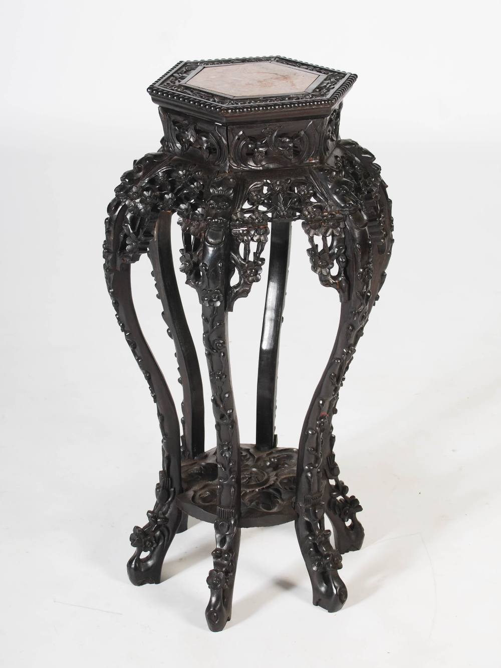 Lot 30 - A Chinese dark wood hexagonal shaped jardiniere stand, Qing Dynasty, the shaped top with a mottled