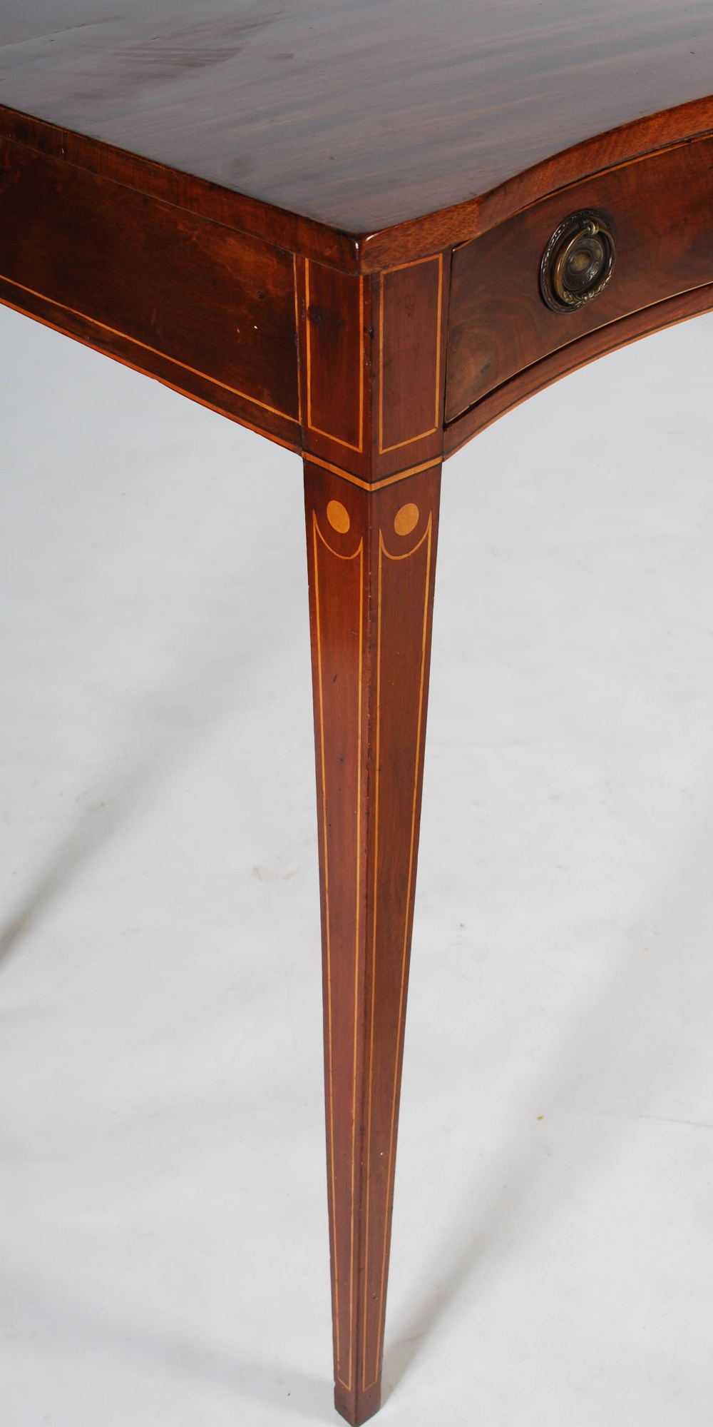 Lot 21 - A George III mahogany and boxwood lined serpentine serving table, the shaped rectangular top above