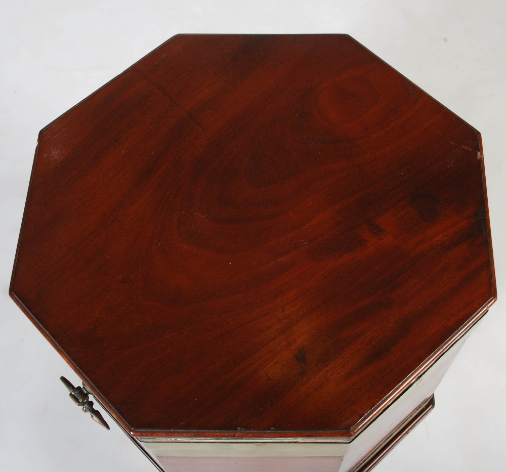 Lot 12 - A George III mahogany and brass bound octagonal shaped cellarette, the hinged cover opening to a