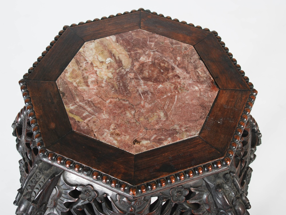 Lot 69 - A Chinese octagonal shaped dark wood jardiniere stand, Qing Dynasty, the shaped top with a mottled