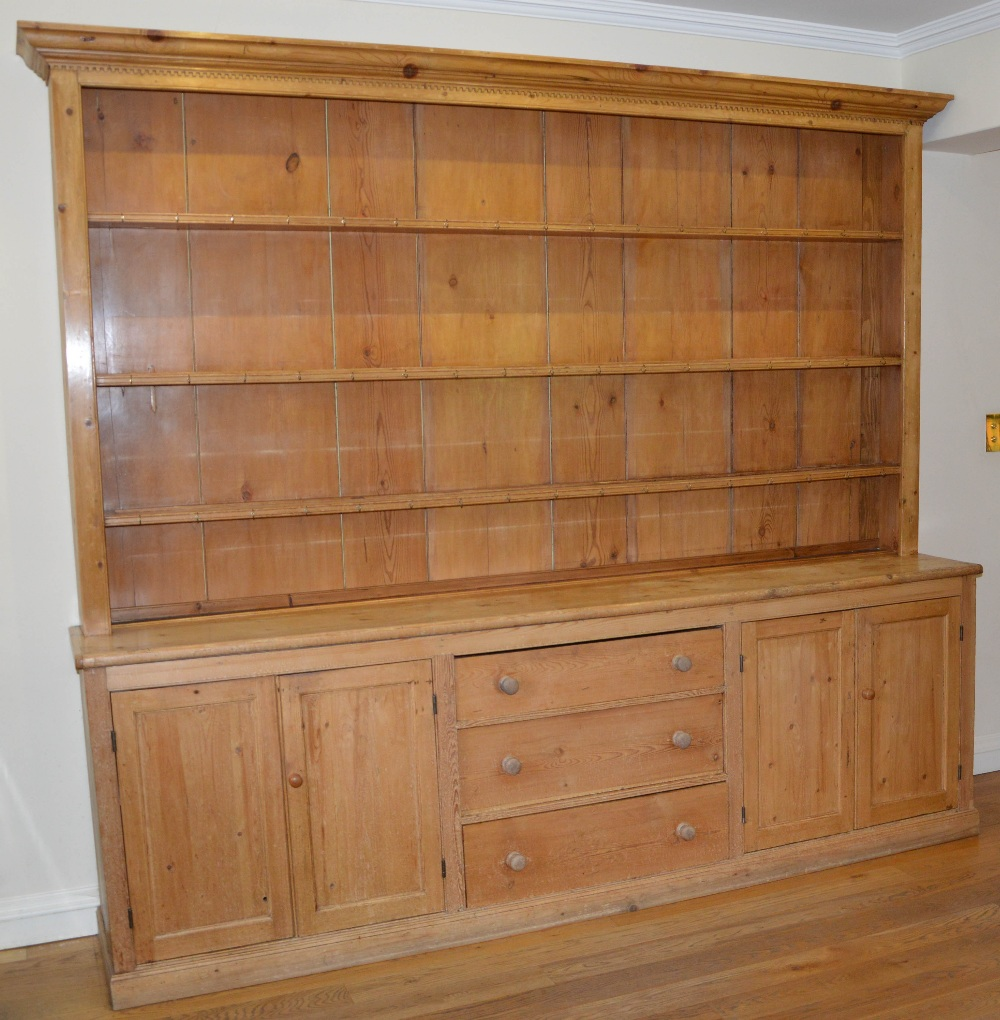 Lot 43 - A late 19th/early 20th century pine country house kitchen dresser, the upper section with moulded