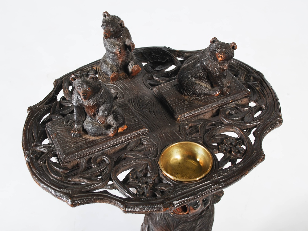Lot 29 - A late 19th/early 20th century Black Forest smokers stand, the upper section carved with a small
