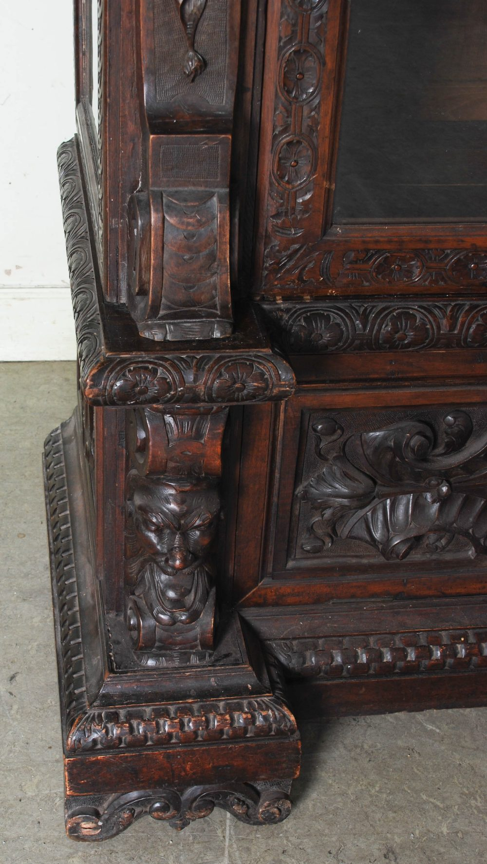 Lot 77 - A late 19th century stained oak display cabinet, with acanthus carved and dentil cornice above a