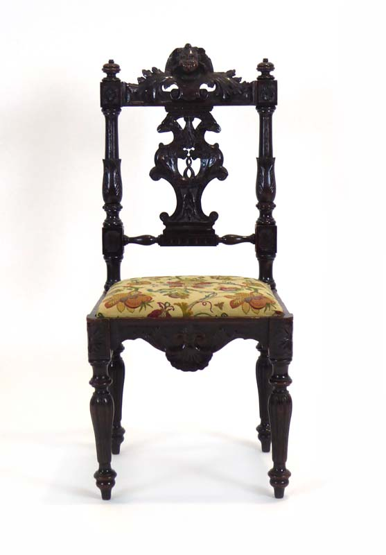 Lot 45 - A 19th century figural carved oak side chair with a drop-in seat over a shaped apron on turned legs