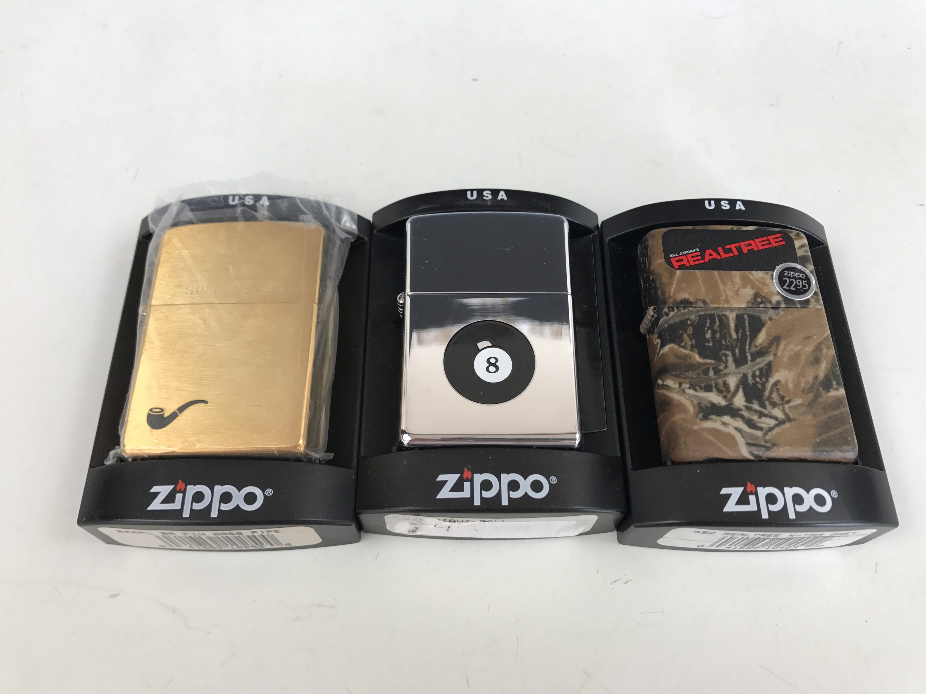 Lot 24 - Three cased Zippo lighters, including No. 204PL BR FIN Brass Pipe, No. 452 Real Tree X-Tra Grey