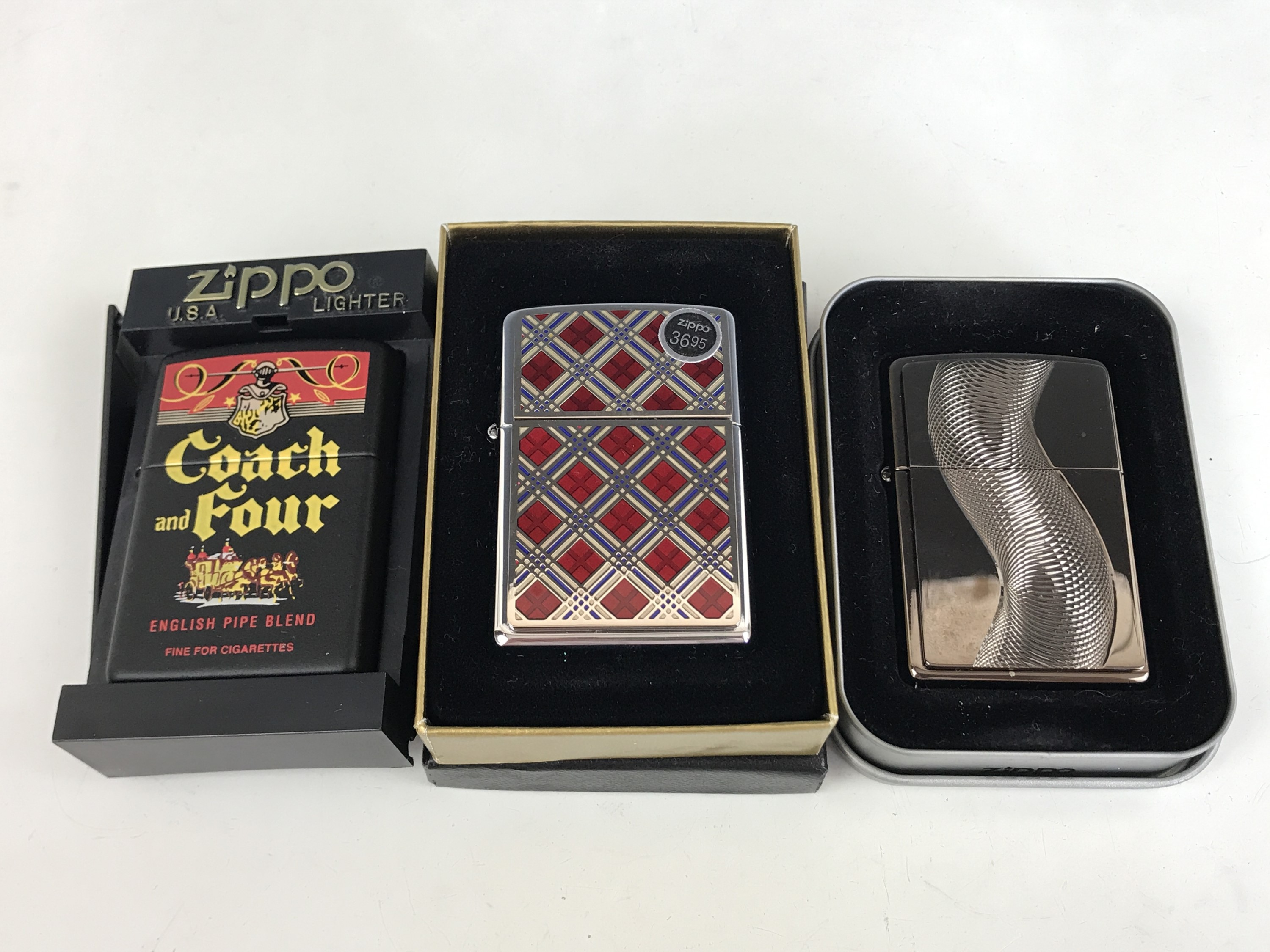Lot 20 - Three cased Zippo lighters, including the Coach and Four from the Tobacco Tin Series, and No.