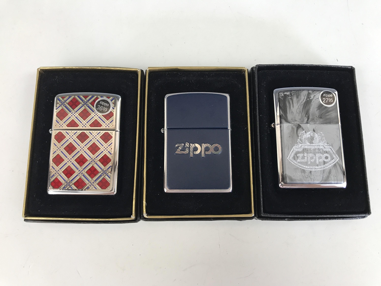 Lot 21 - Three cased Zippo lighters, including No. 20429 Cherry Plaidness Emblem, No. 200 Blue and Chrome,