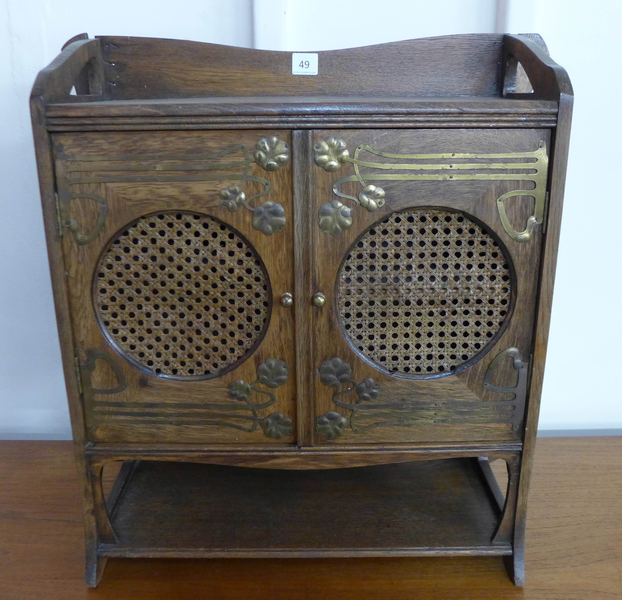 Lot 49 - An Arts and Crafts oak and brass mounted table top cabinet