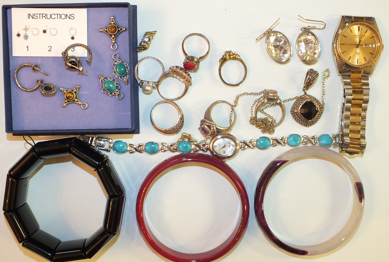 Lot 265 - A purple and white banded agate bangle, a pink hardstone bangle, a bracelet of onyx plaques, a