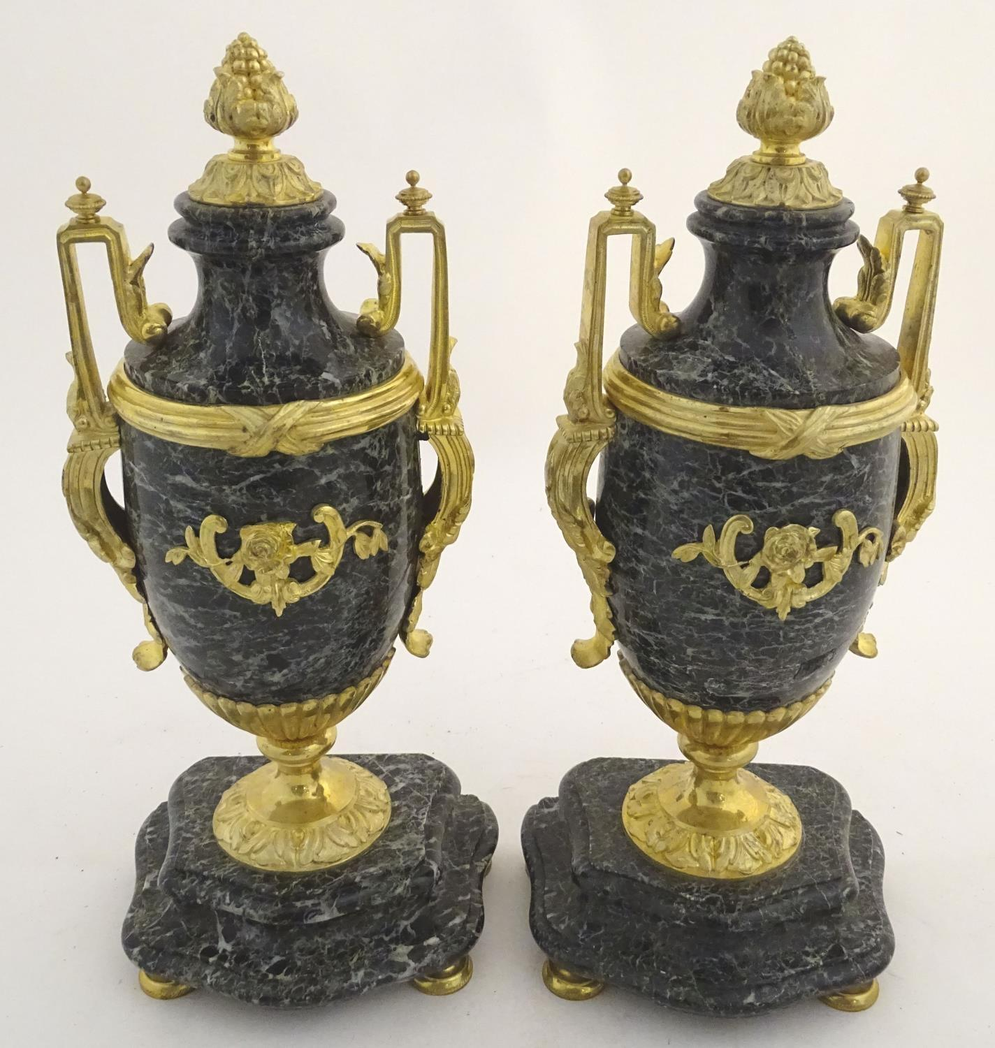 A pair of late 19thC grey marble garnitures of urn form with gilt metal handles and mounts.