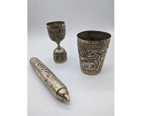 An Indian silver tumbler, decorated with elephant and rabbits,H.9cm, together with a pierced silver scroll case and and Easte