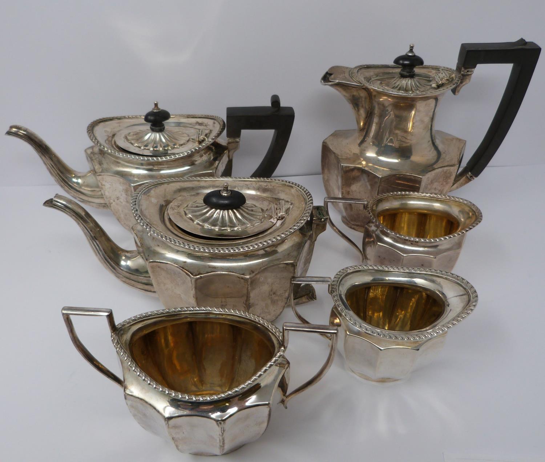 A silver six piece tea service with ebony handles and finial, coffee pot, tea pots, water jug, two