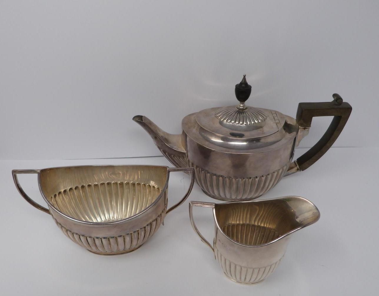 A three piece silver tea set, sugar, tea pot and milk jug, tea pot and helmet jug Ebony handle by