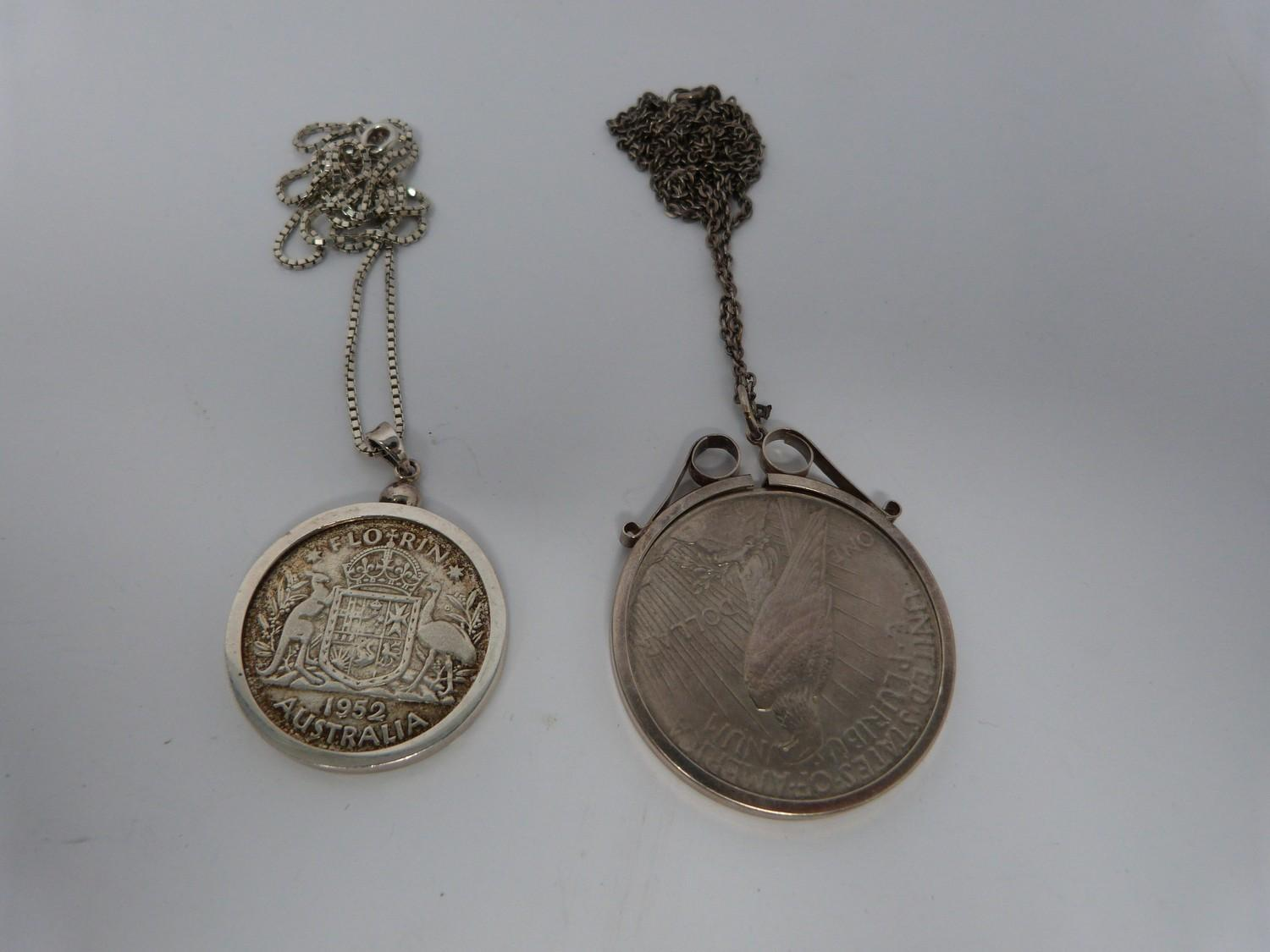 Two silver coins in silver and white metal mounts on silver chains, an American one dollar coin,