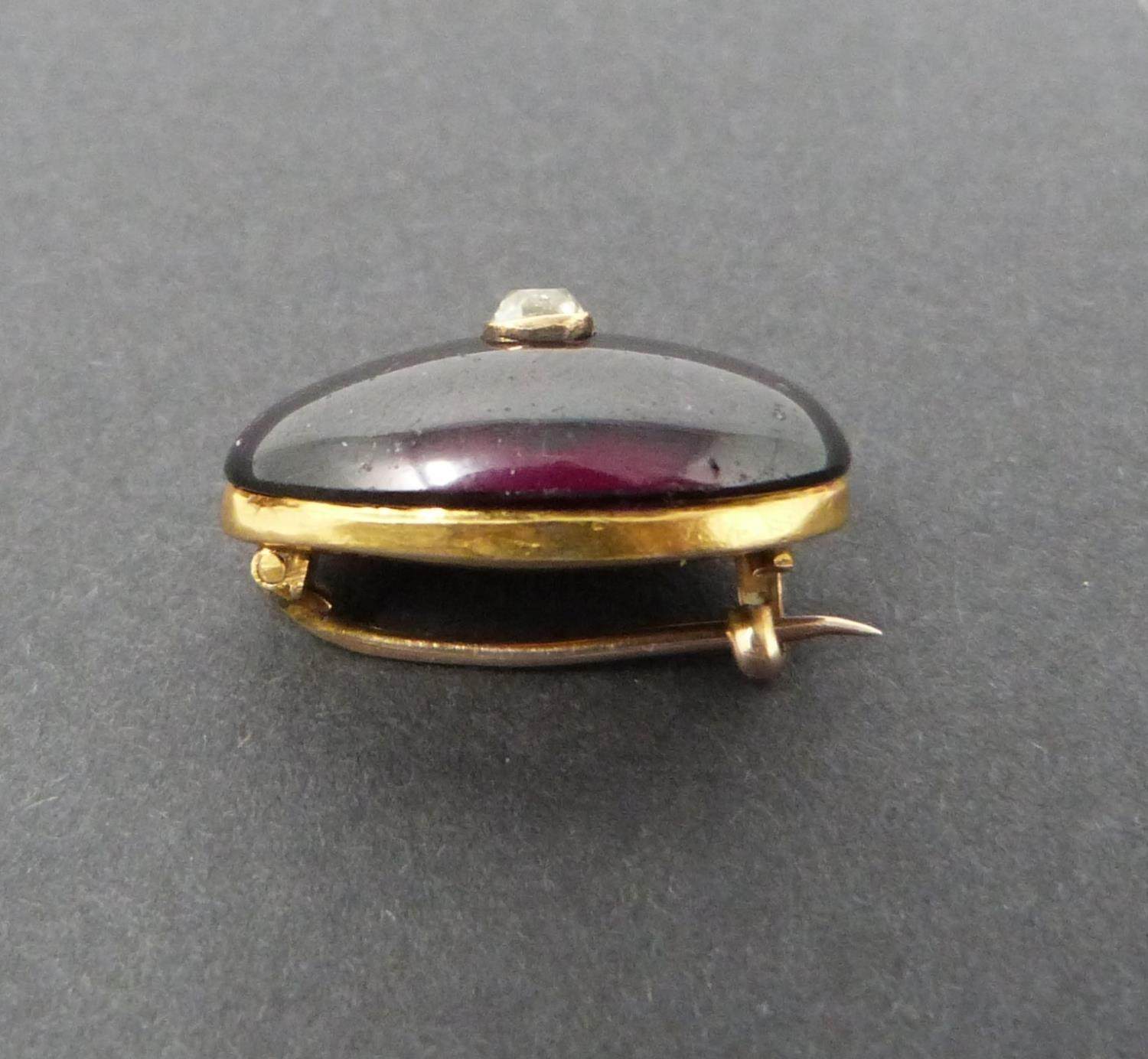 A Georgian/Victorian yellow metal oval garnet brooch inset with diamond, hollow foil backed cabochon - Image 3 of 6