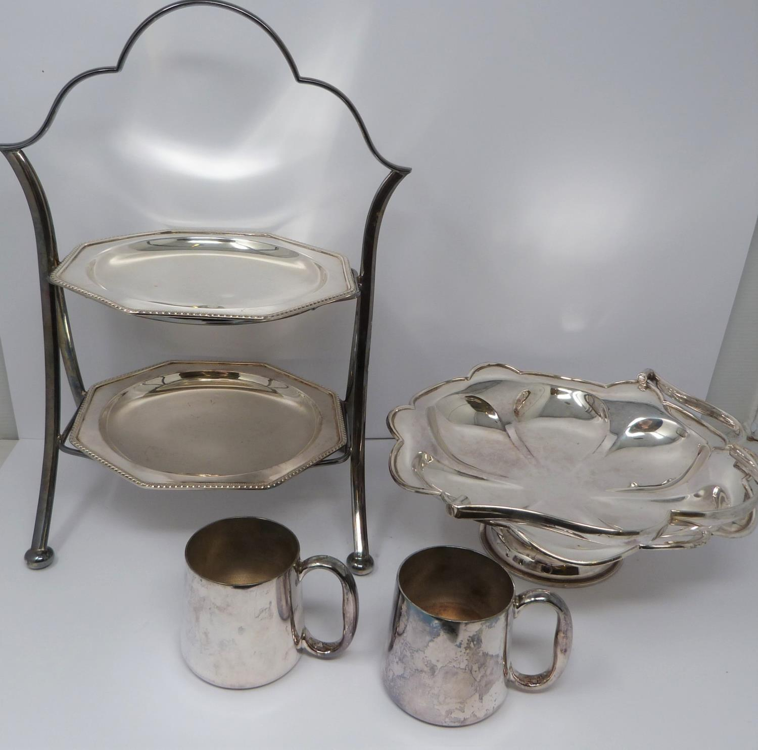 A silver plated cake stand, handled basket and two tankards, basket stamped EPNS, 13694, flower form