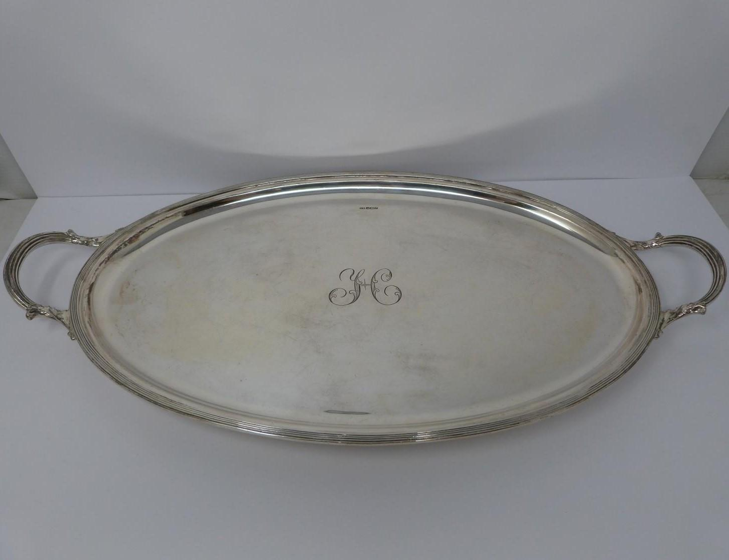 A large silver oval tray, monogrammed with H, round pebble feet, foliate design handles, ridged rim,