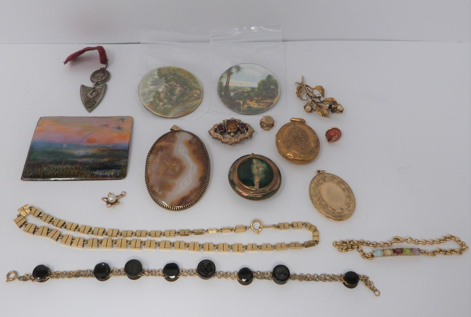 A collection of gold plated and yellow metal jewellery including enamel plaques, coral snake