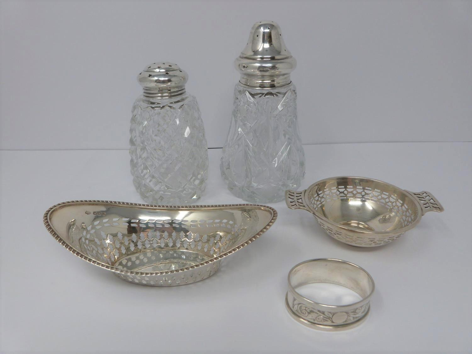 Two silver and cut glass sugar sifters, two silver pierced dishes and a silver engraved napkin ring,