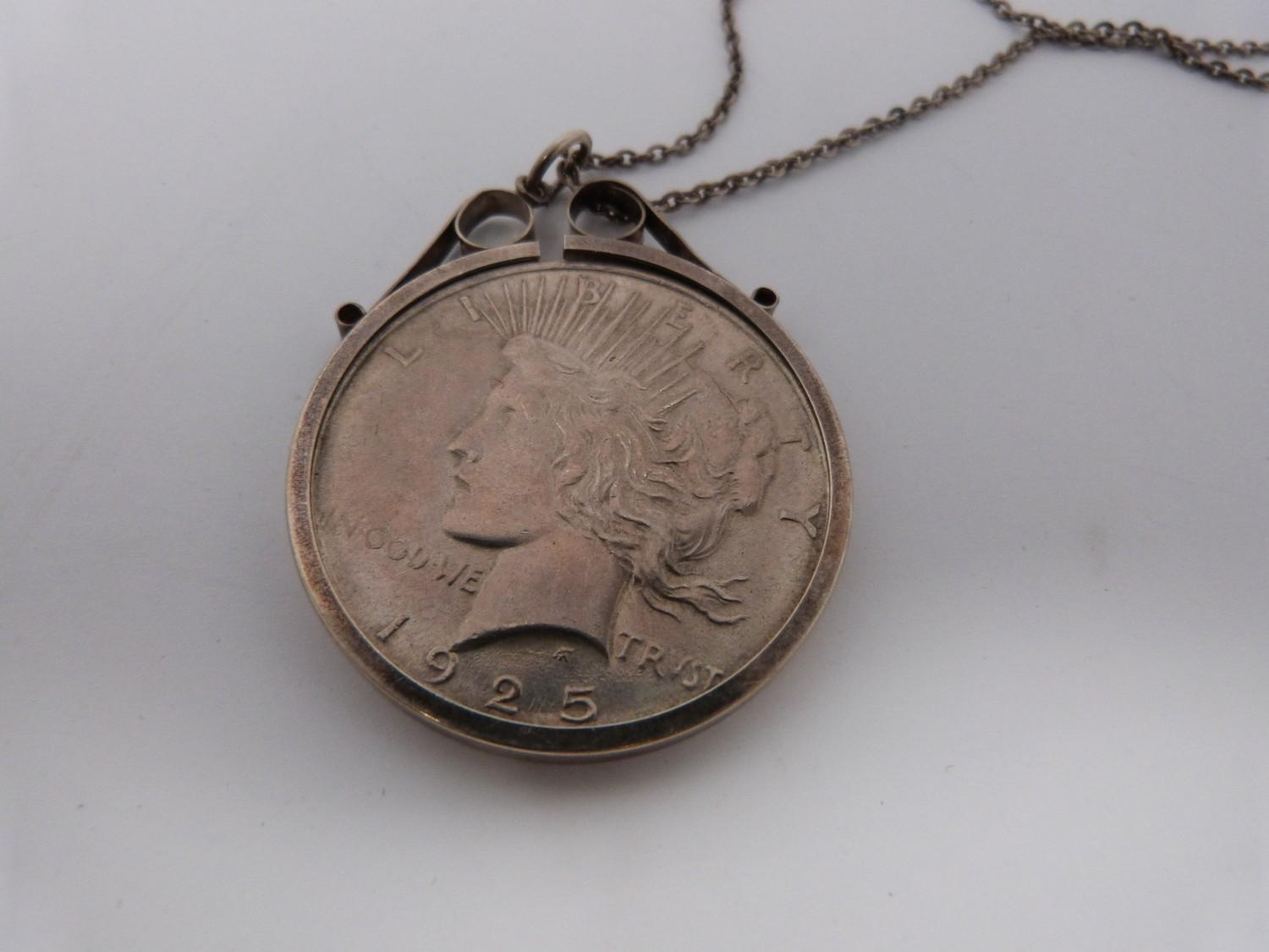 Two silver coins in silver and white metal mounts on silver chains, an American one dollar coin, - Image 3 of 6