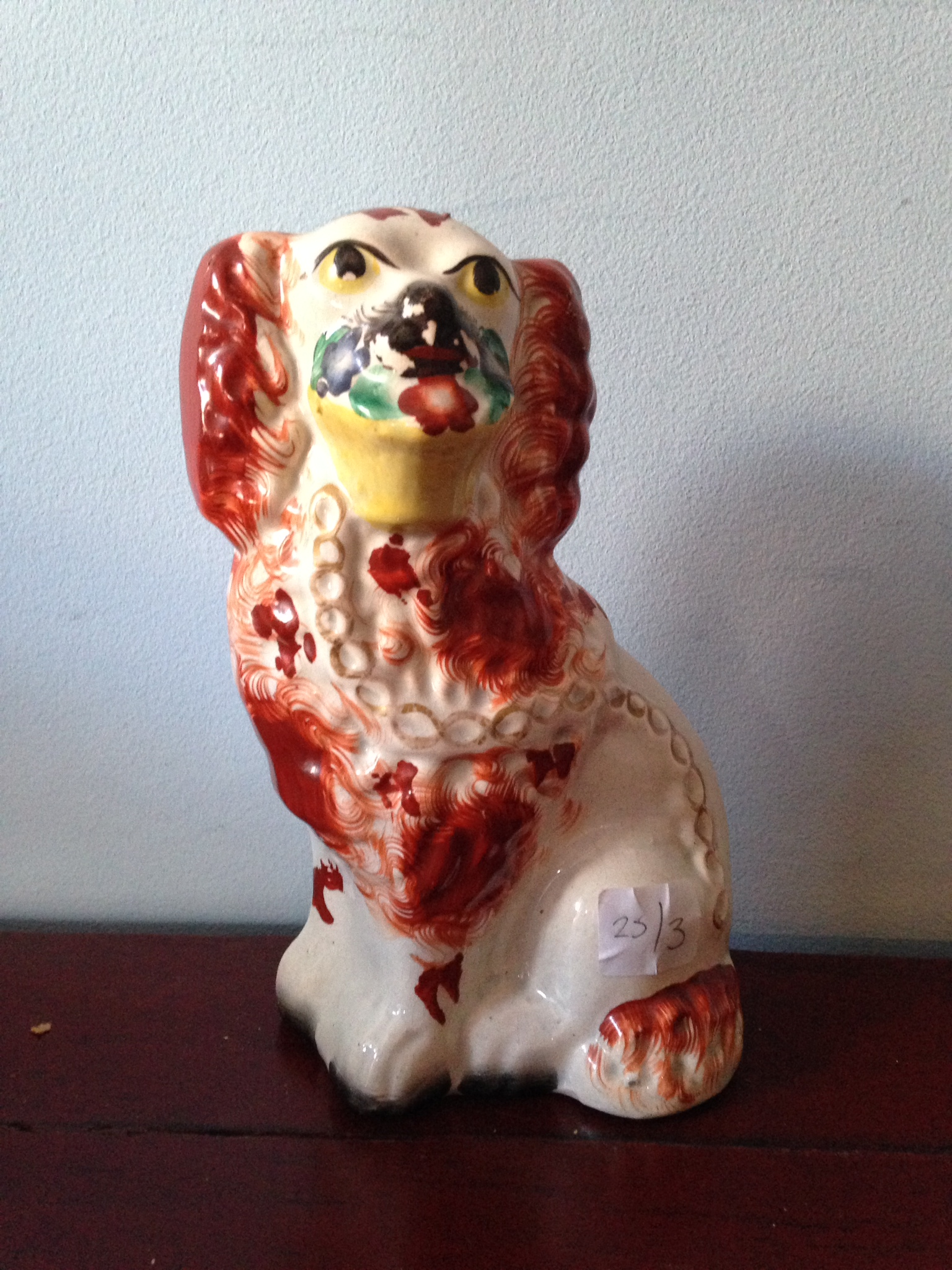 Lot 18 - A 19th c Staffordshire dog with basket in mouth 20cm high