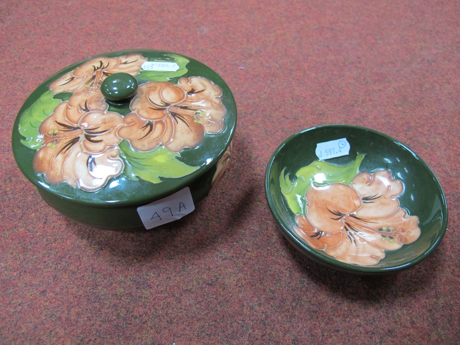 Lot 49A - A Moorcroft 'Hibiscus' Circular Bowl and Cover, together with a matching dish. (2)