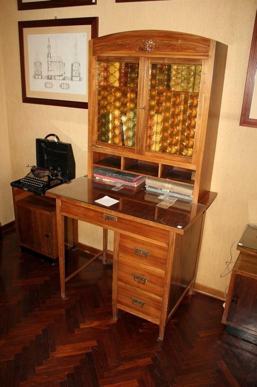 Lot 34 - Scrivania periodo liberty a quattro cassetti con alzata a due ante in vetro, cm. 90x65xh175