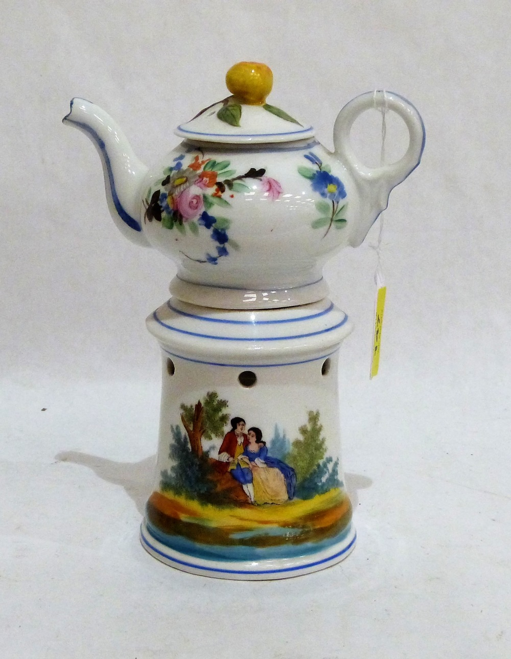 Lot 147 - A 19th century French veilleuse teapot on burner stand, painted in colours with lovers in a garden