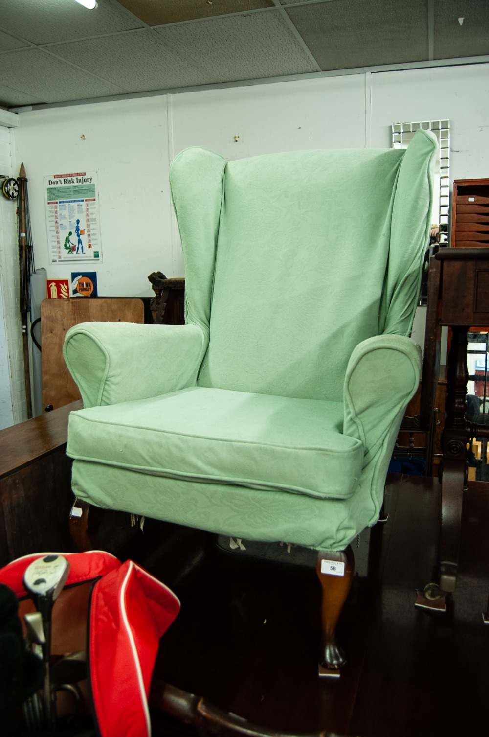 Lot 58 - A FIRESIDE ARMCHAIR, RAISED ON CABRIOLE SUPPORTS