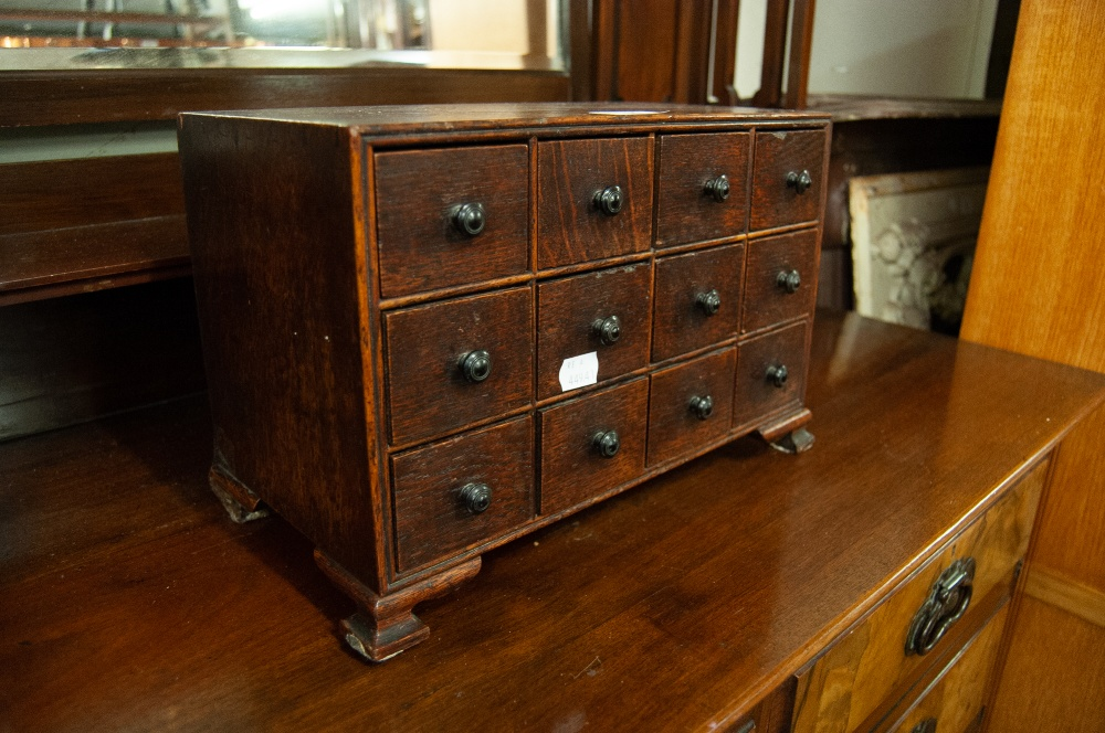 Lot 50 - AN OAK MINIATURE TABLE TOP CHEST OF DRAWERS, TWELVE BOX DRAWERS WITH TURNED HANDLES ALL RAISED ON