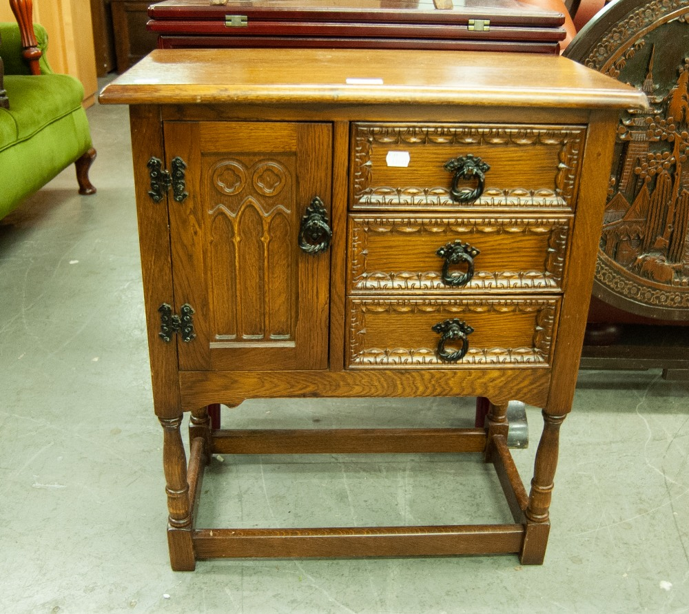 Lot 27 - AN OAK SMALL CABINET WITH THREE DRAWERS AND A CUPBOARD WITH CARVED DECORATION TO THE FRONT