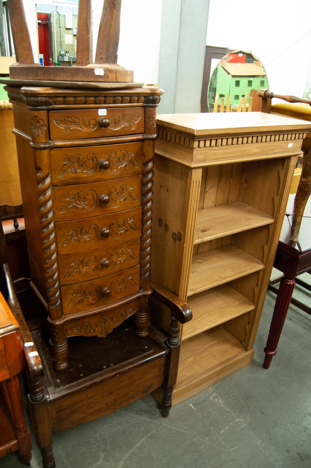 Lot 26 - A NARROW PINE OPEN BOOKCASE WITH ADJUSTABLE SHELVES AND A NARROW CHEST OF SIX DRAWERS WITH CARVED