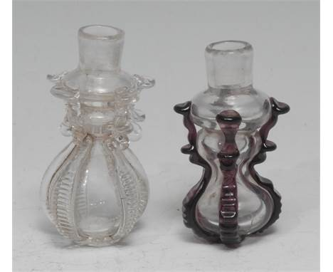 A small 18th century cruciform glass flask or phial, hourglass reservoir applied with purple lugs, 6cm long; another, clear g
