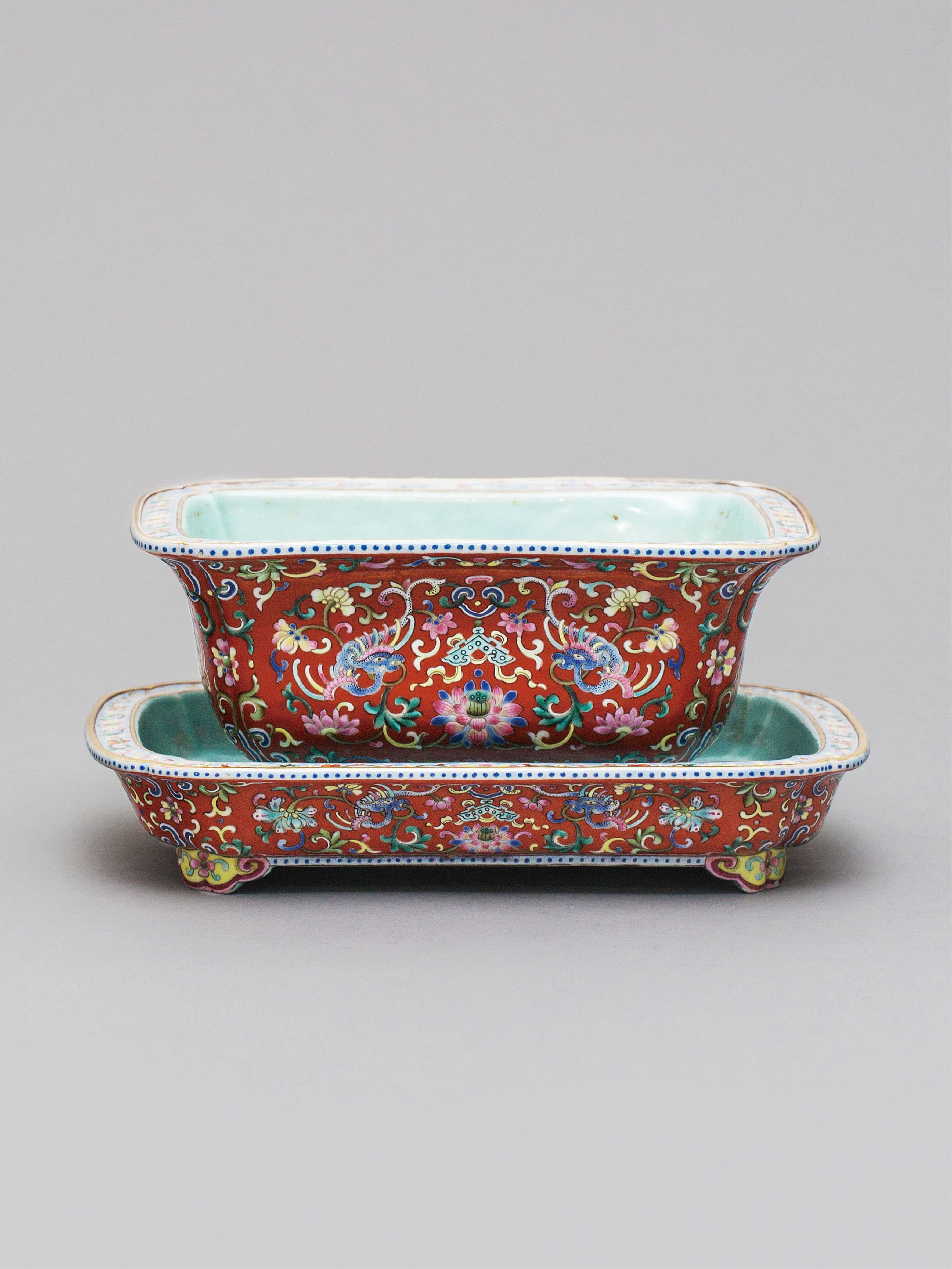 Lot 36 - A coral- ground 'famille-rose' jardiniere and stand, Qing Dynasty, Qianlong period