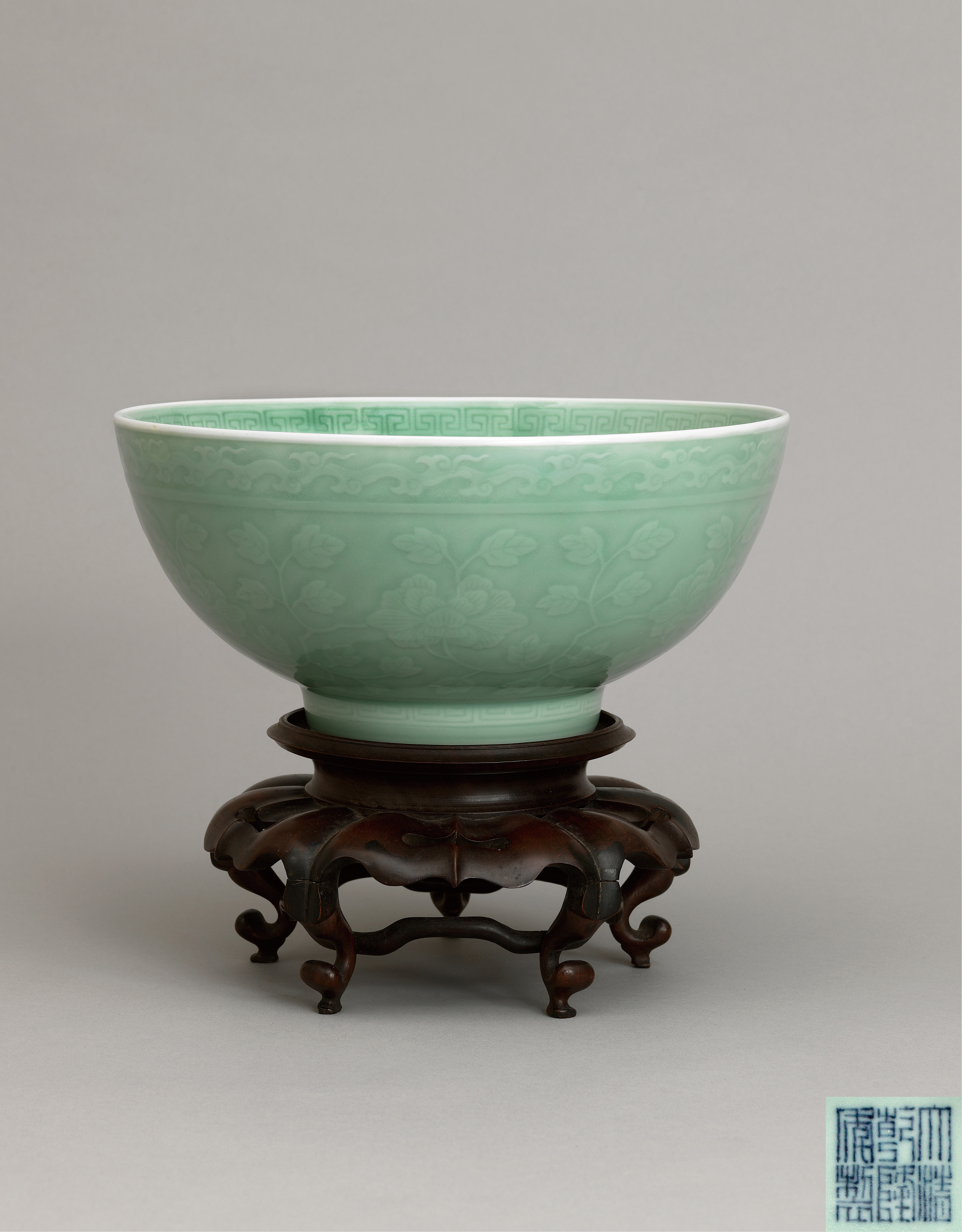 Lot 5 - A large celadon-glazed 'peony scroll' bowl,Qianlong six-character seal mark and of the period
