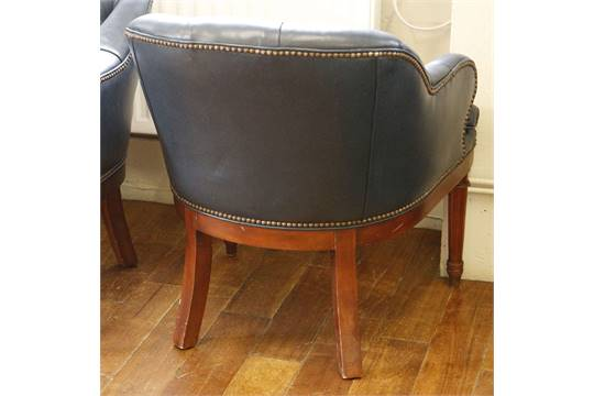 A set of four blue leather button-back club tub chairs with brass ...