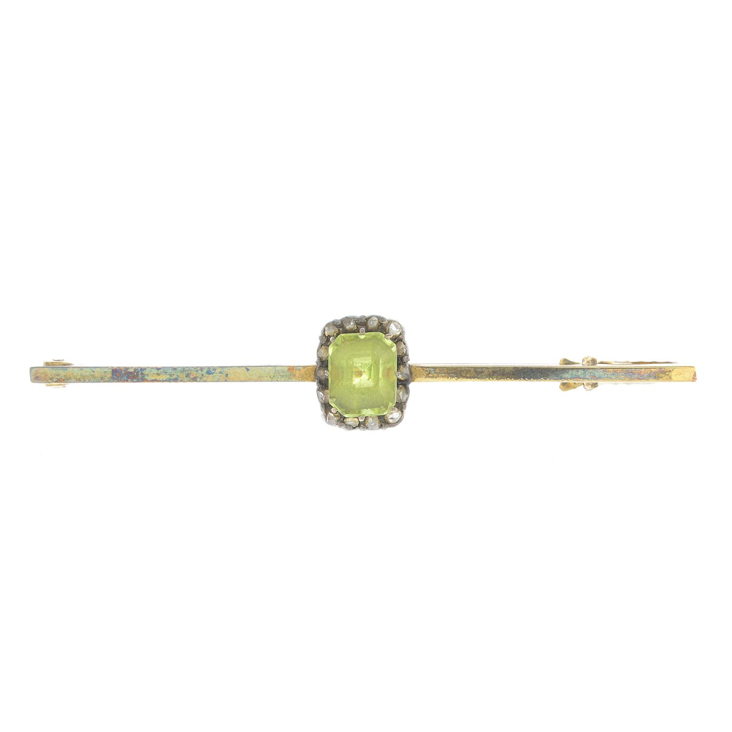 Lot 30 - An early 20th century silver and gold peridot and diamond bar brooch.Length 5.1cms.