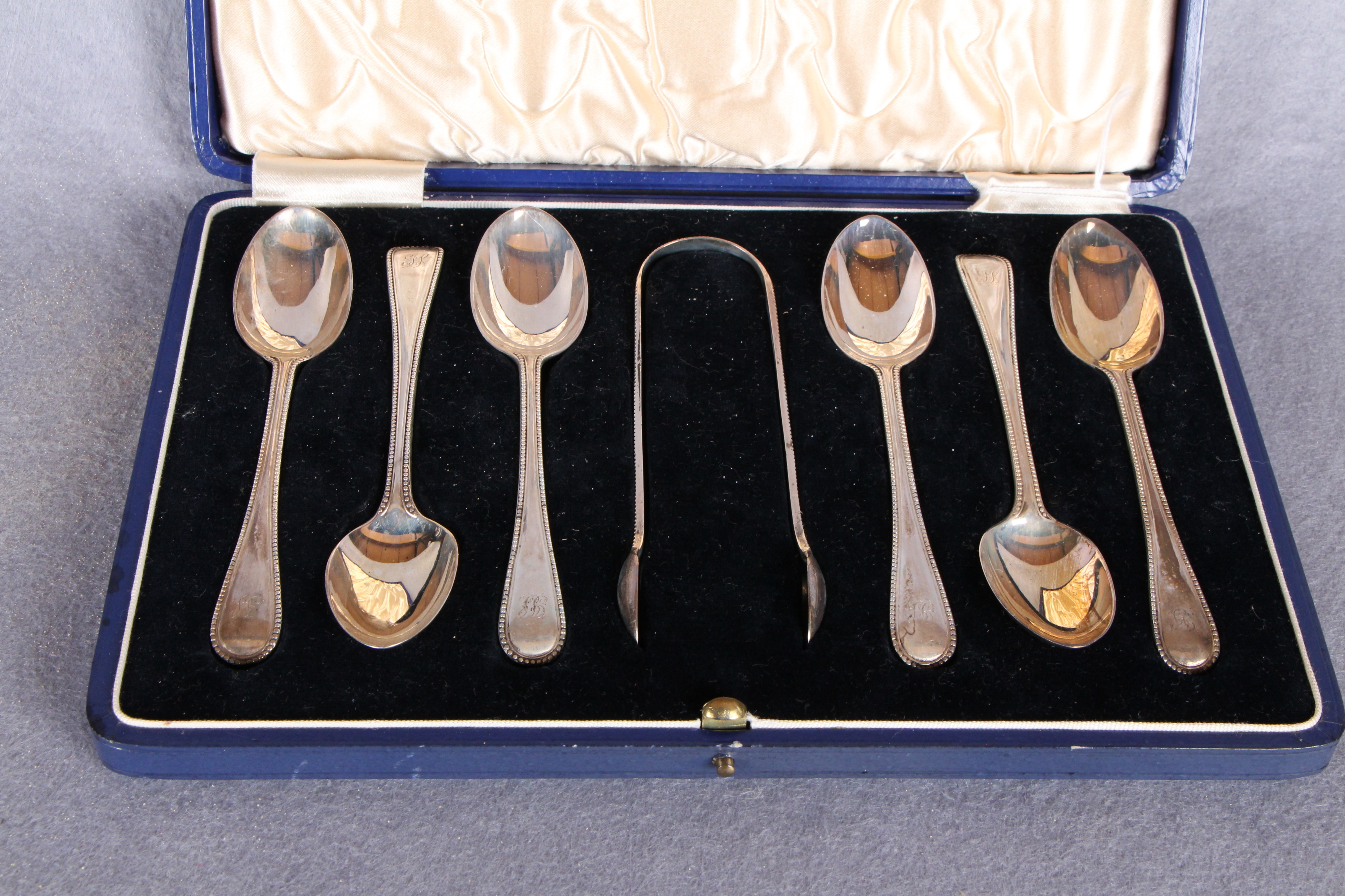 Lot 40 - A set of six beaded Old English pattern teaspoons and tongs, engraved initials, London 1872,