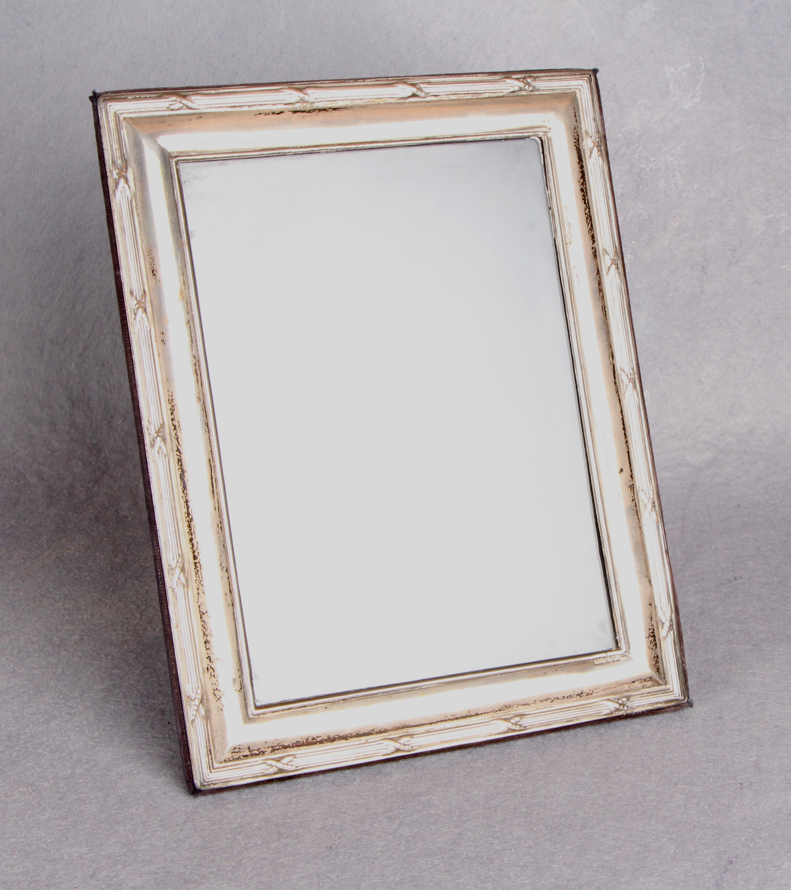 Lot 39 - A rectangular picture frame with ribbon tied and reeded border, strut support,