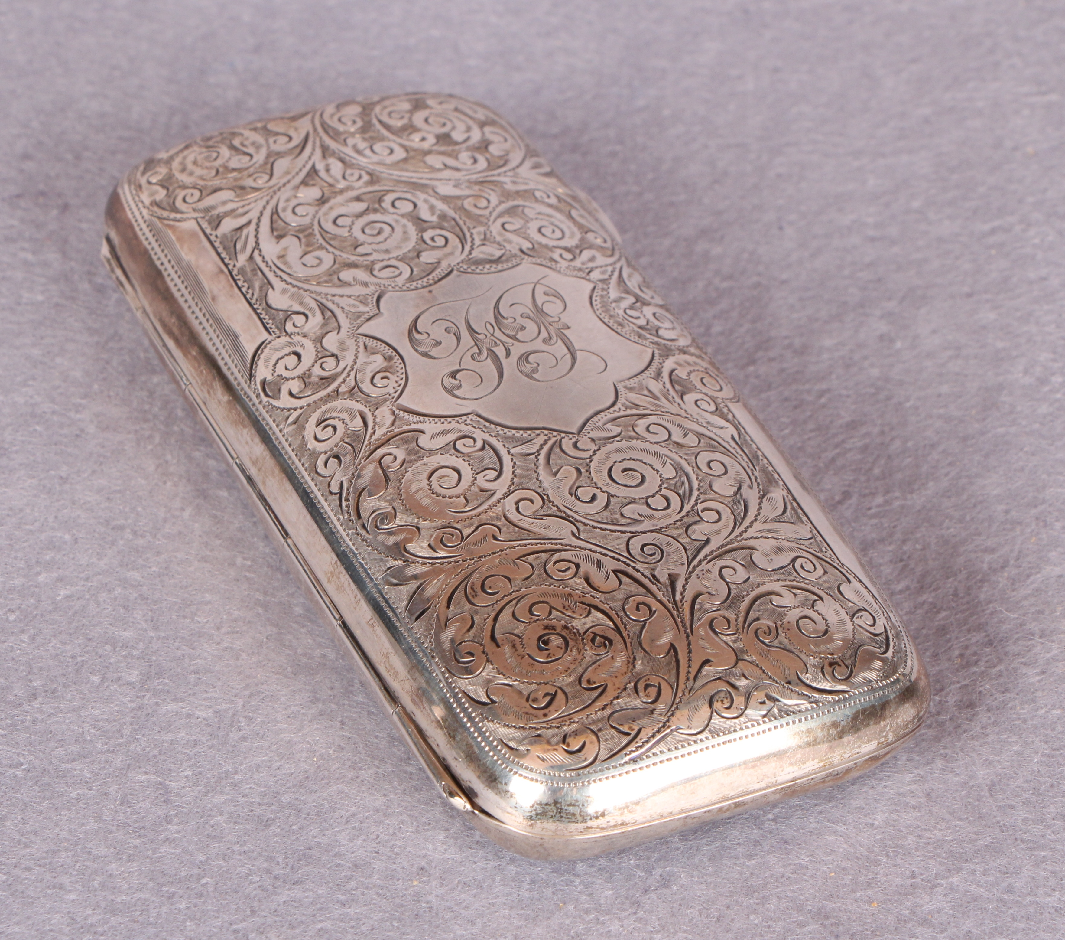 An Edwardian cigar case, overall engraved with foliage, the interior gilt,