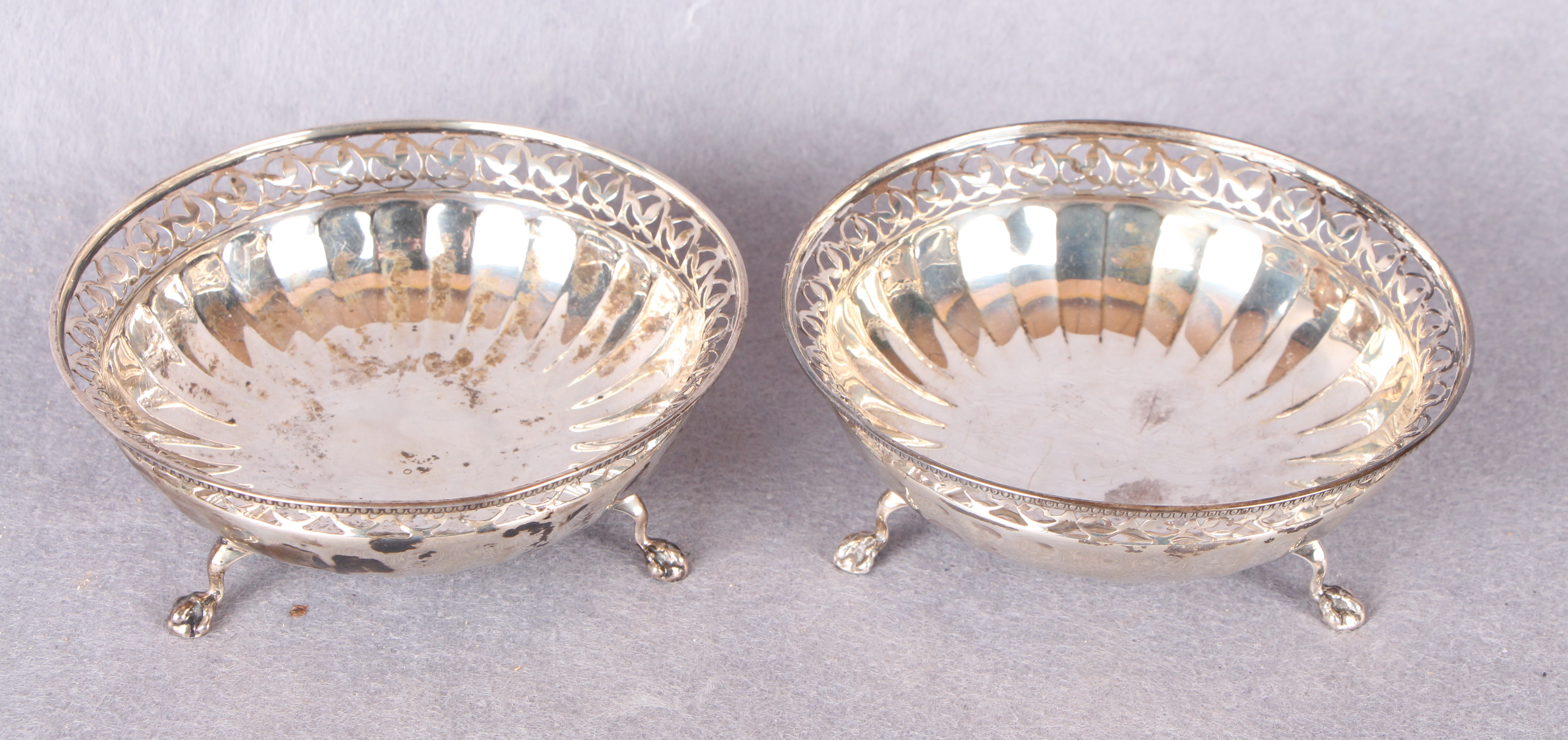 Lot 50 - A pair of circular bon-bon dishes with pierced rims and semi fluted bases, three claw and ball feet,