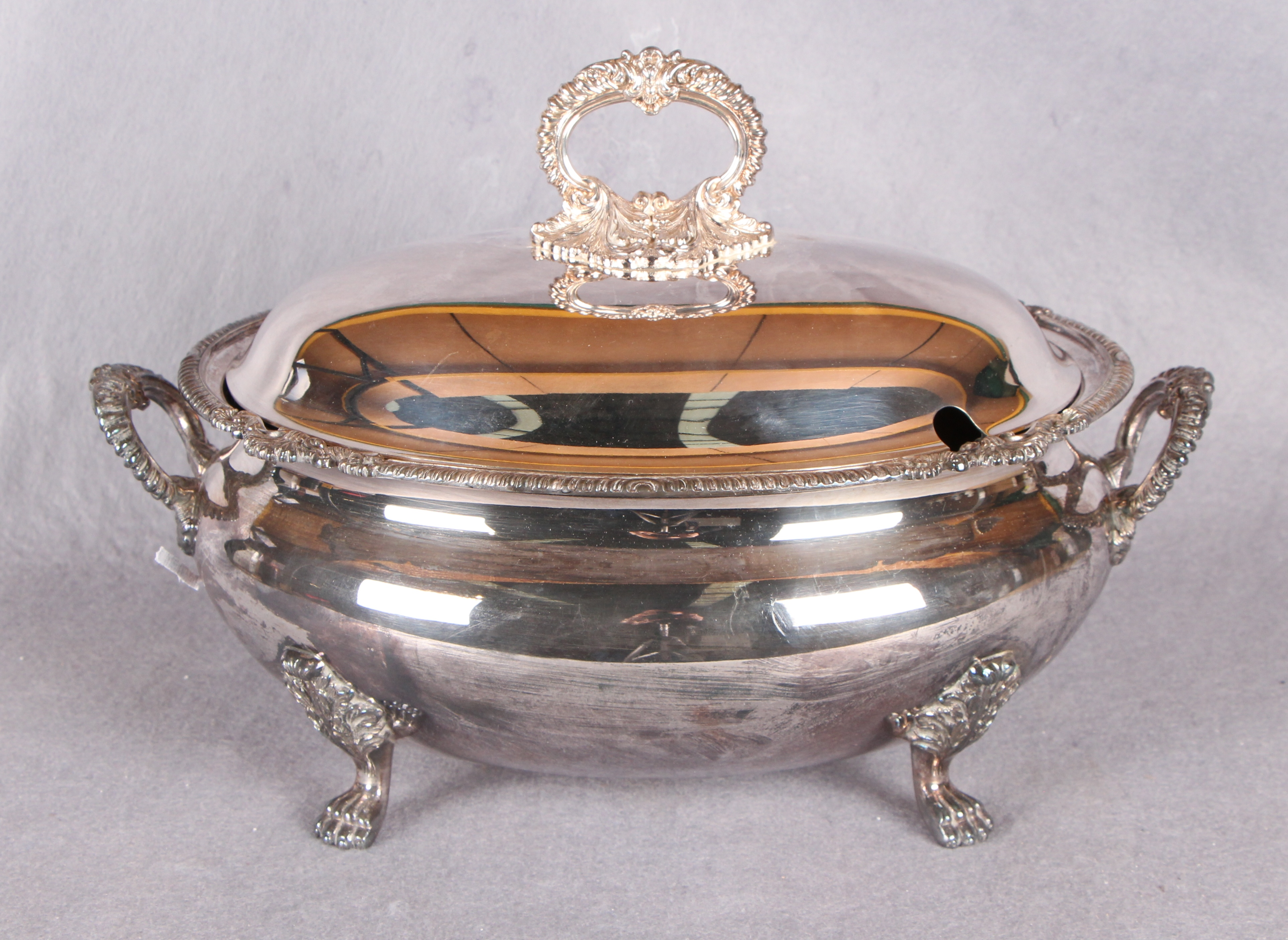 "Lot 3 - An oval soup tureen and cover, with cast borders, handles and lion paw supports, stamped ""Harrods,"