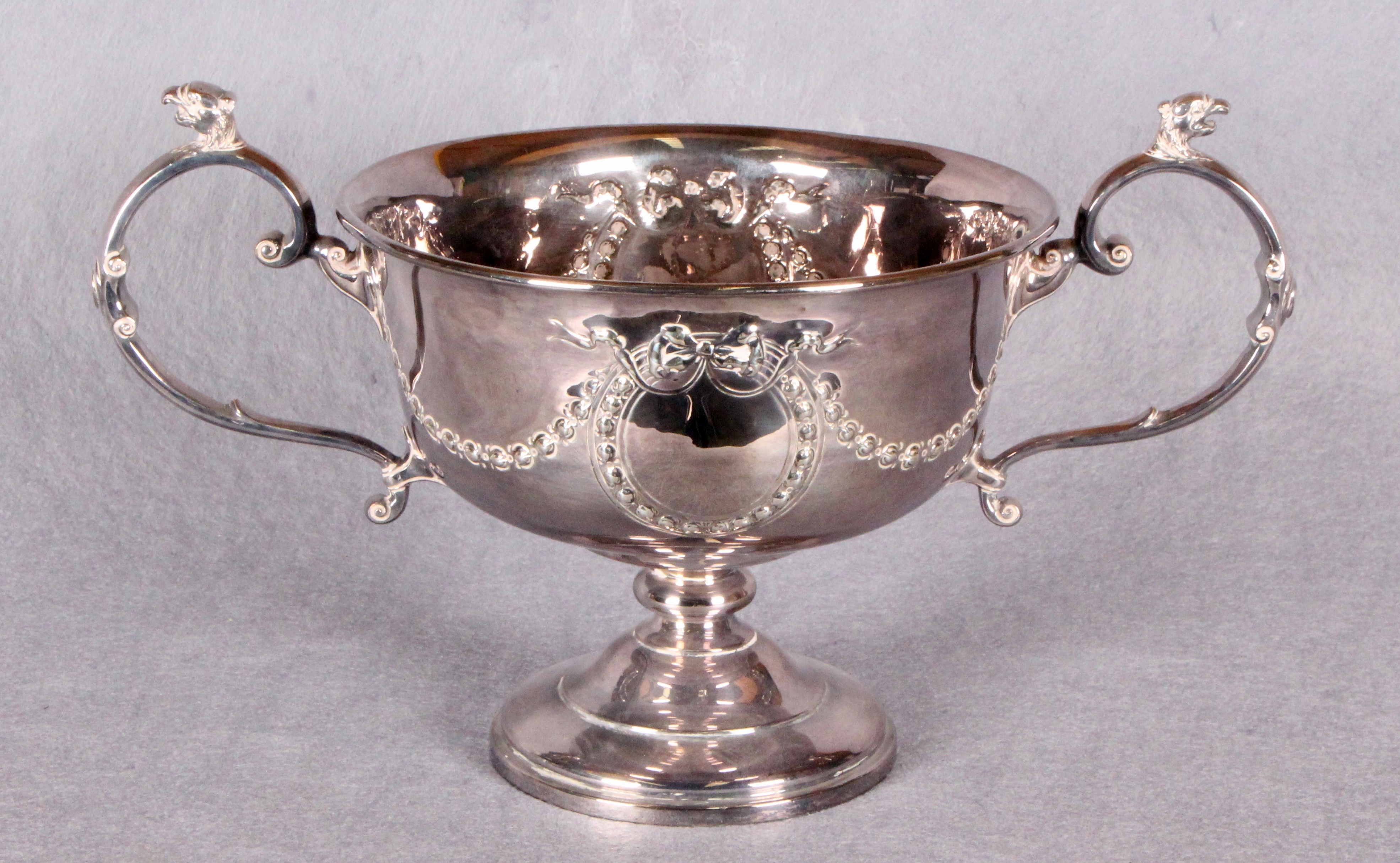 Lot 42 - A two-handled pedestal rose bowl, repoussé with swags of ribbon tied floral branches, circular base,