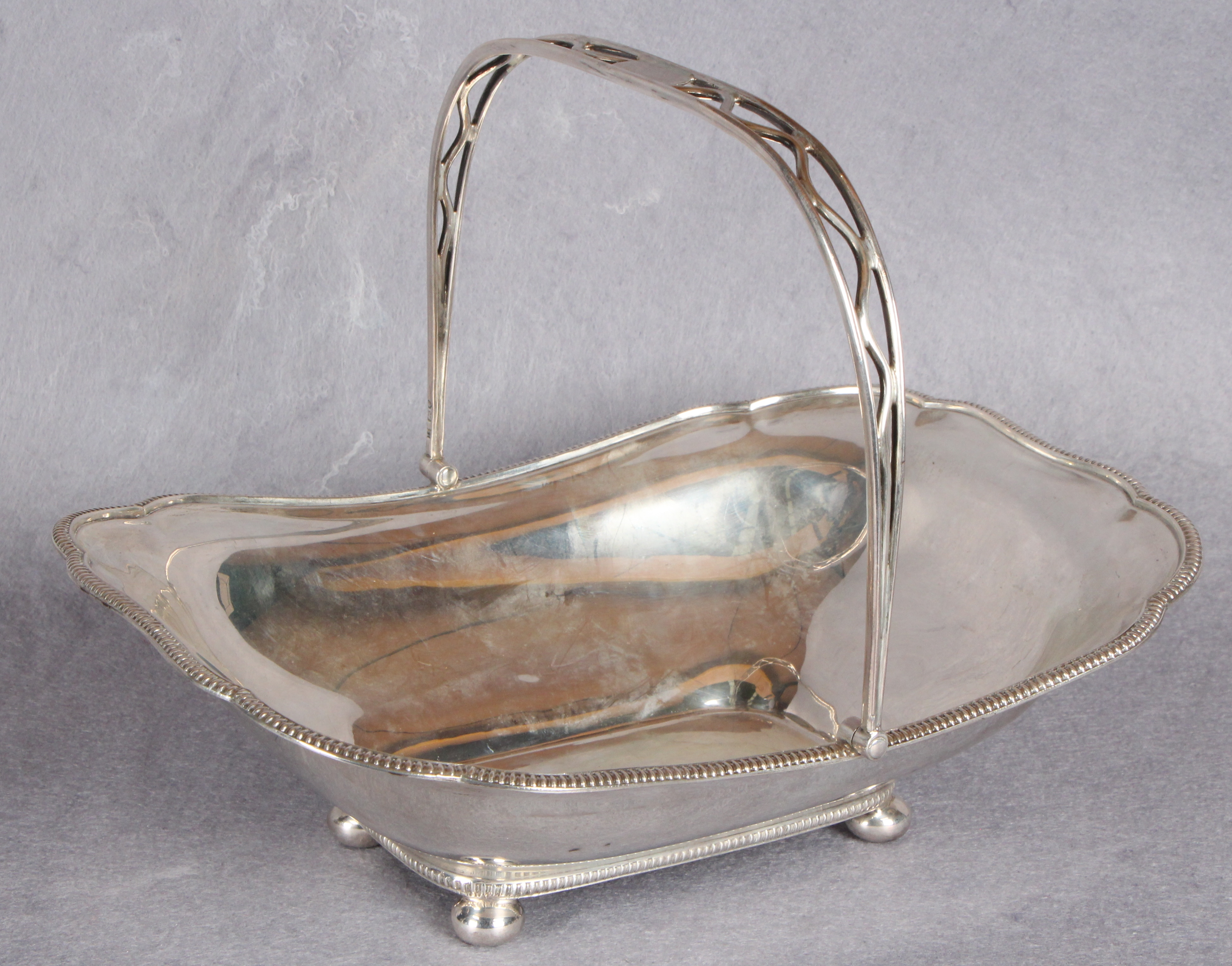 Lot 58 - A shaped rectangular cake basket with swing handle, four ball feet,