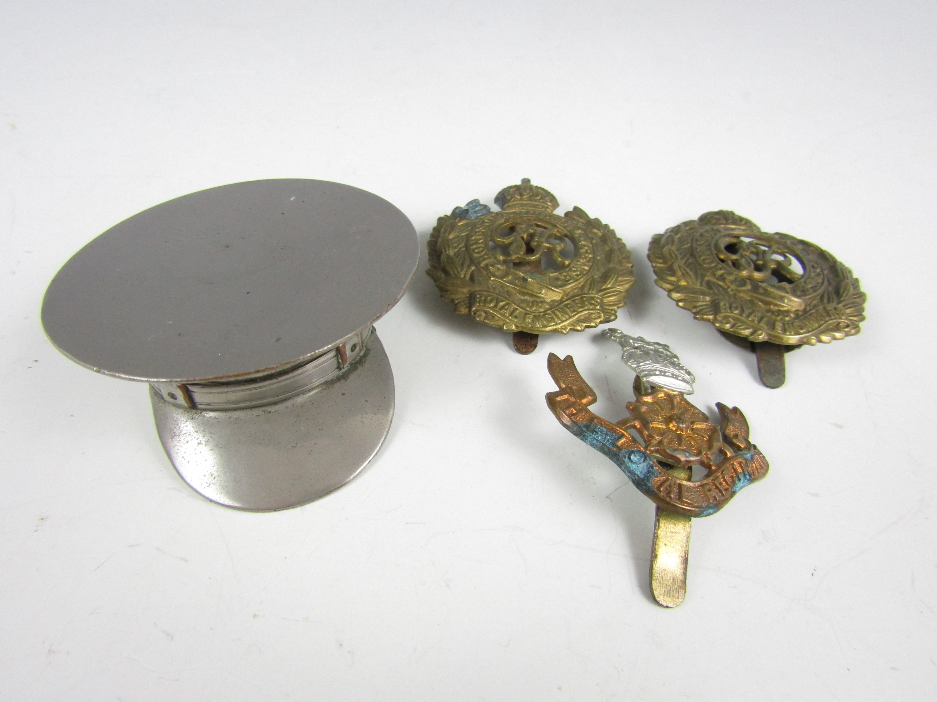 Lot 18 - A novelty electroplate cap together with three cap badges