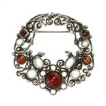 AN ANTIQUE ARTS & CRAFTS MOONSTONE AND GARNET BROOCH, ATTRIBUTED TO DORRIE NOSSITER in silver set