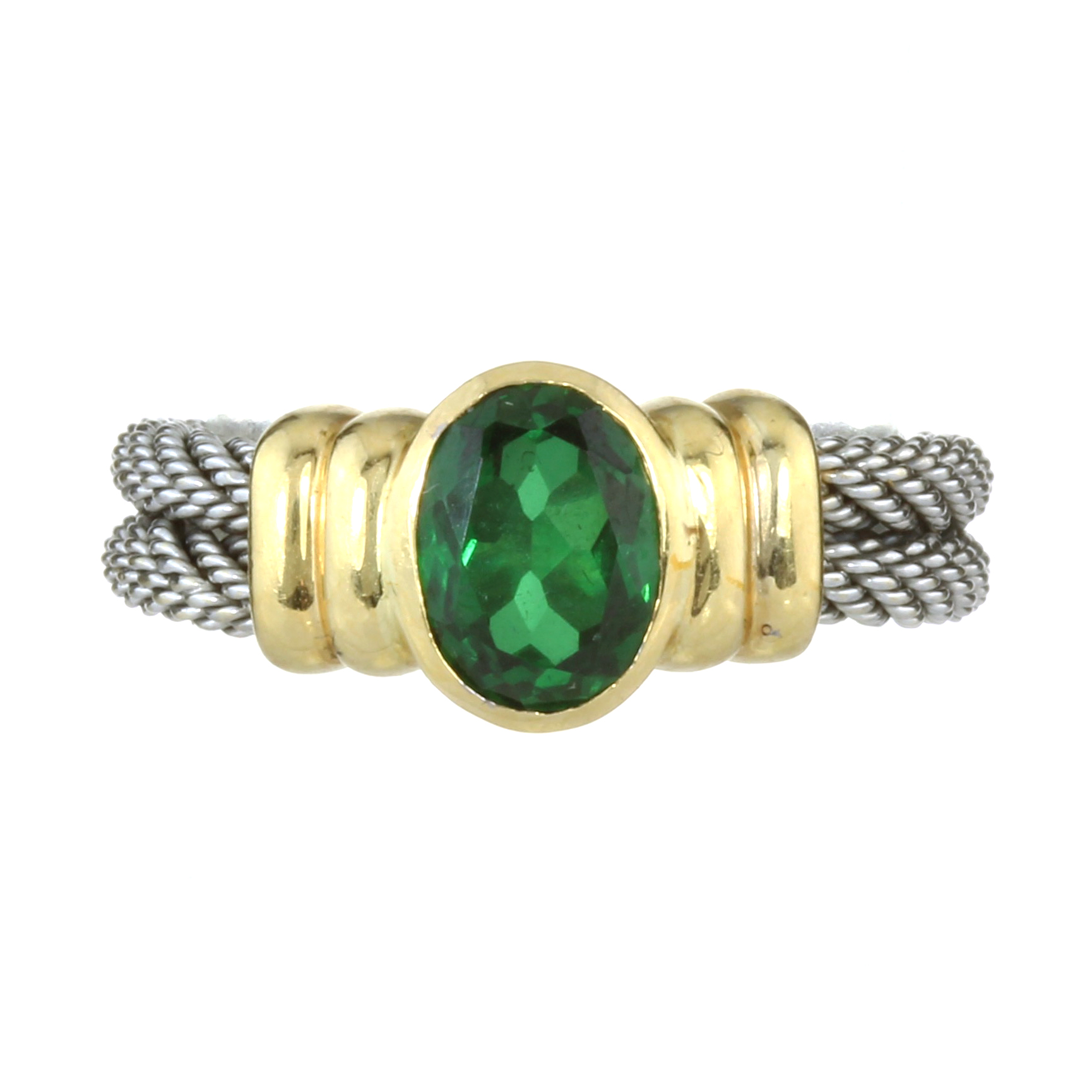 A TOURMALINE DRESS RING in yellow and white gold, the oval green tourmaline collet set between